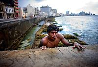 Portrait in Havana, Cuba of man climbing coastal wall.