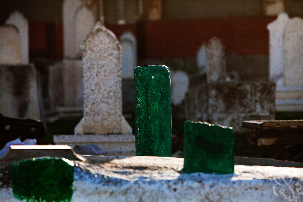Green paint marks the graves of the Samouni family members December 19, 2009 in Gaza City, Gaza. The Samouni family is synonymous with the 22 day Israeli offensive in Gaza last year during which 29 members of the family were killed in the Zeitoon district of Gaza City. A year later, Palestinians across the tiny strip continue to struggle daily in various ways economically, physically, and emotionally. .