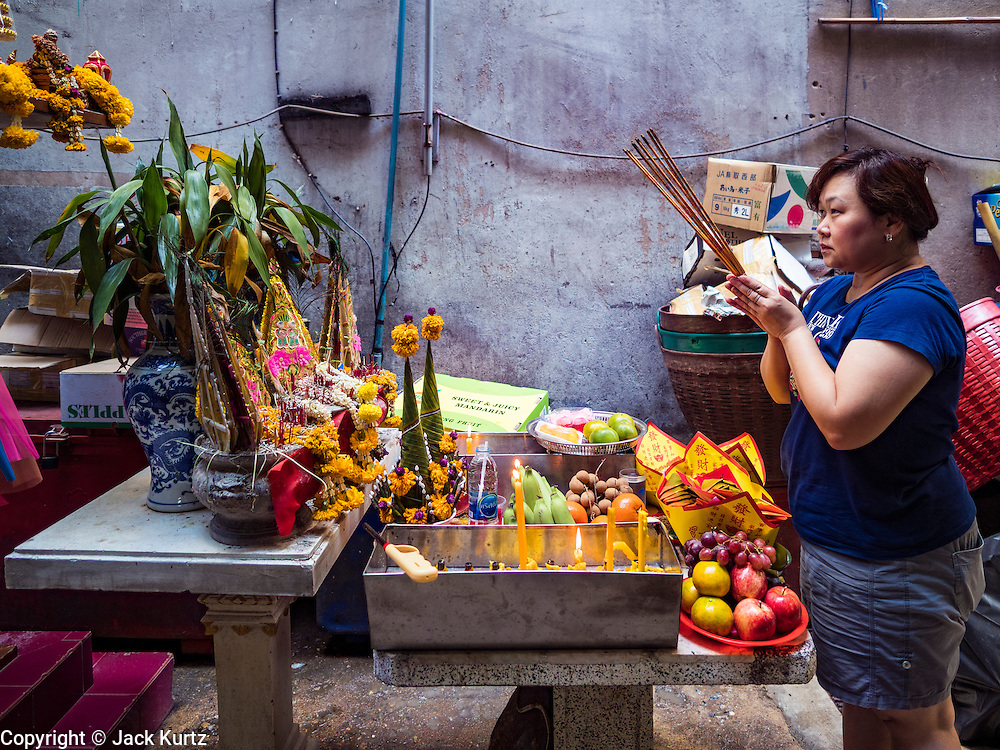 27 JANUARY 2017 - BANGKOK, THAILAND: A woman prays for a prosperous new year at a local shrine on Chinese New Year in Bangkok. 2017 is the Year of the Rooster in the Chinese zodiac. This year's Lunar New Year festivities in Bangkok were toned down because many people are still mourning the death Bhumibol Adulyadej, the Late King of Thailand, who died on Oct 13, 2016. Chinese New Year is widely celebrated in Thailand, because ethnic Chinese are about 15% of the Thai population.       PHOTO BY JACK KURTZ