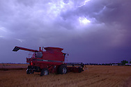 A Case IH combine rests in a field of recently harvested winter wheat as a violent thunderstorm with lots of lightning approaches on the prairies of Illinois.