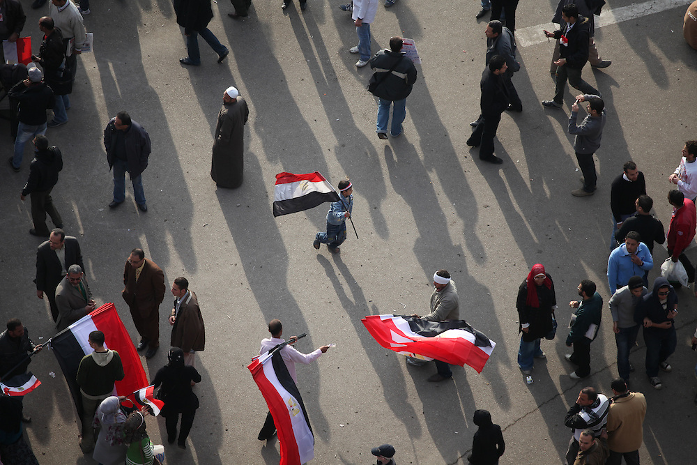 A boy runs with a freshly purchased Egyptian flag at Tahrir Square on 10 February.