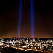 Two beams of light illuminate the spires of the Portland Convention Center and reach 1000 feet upward  in memorial to those who gave their lives in the September 11th attacks. The view from atop the Kaiser Permanente building also picks up refracted red light from the tower lights.