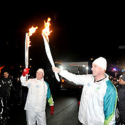 Gold medal winning Olympic athlete Matthew Pinsent transfers the Olympic flame to former Whistler Mayor and fellow torch bearer Drew Merideth during his Olympic torch run.  February 5th, 2010.  Whistler BC, Canada..David Buzzard/From the Canadian Press