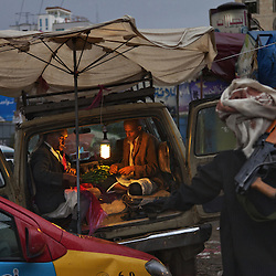 A man holding an AK-47 passes by as Muhammad Ali Jobebi, left, and his son prepare bundles of qat, a popular stimulant leaf, at a bazaar in Sana, Yemen, Nov. 13, 2012. Once best known for its coffee, Yemen now devotes 40 percent of its scarce water to irrigating qat. Worth $1.2 billion a year, the qat trade can earn sellers one thousand dollars per day. Meanwhile most of the country's food is imported.