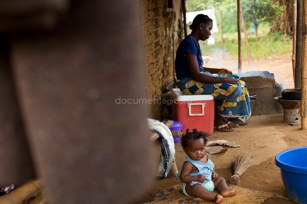 Woman and child on the porch of their house, Kingsville #7, Liberia.