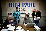 Volunteer Robert Terhune, center right, signs up volunteers at Ron Paul's presidential campaign headquarters in Reno, Nev., January 31, 2012.