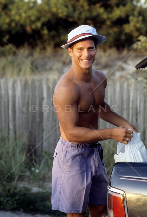 man without a shirt smiling and wearing a retro hat