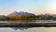 The Golden Ears mountains are a familiar sight from the Fraser Valley (especially Langley and Maple Ridge).  This view is photographed from Brae Island Regional Park in Langley, British Columbia with the Fraser River log booms in the foreground.  The Golden Ears (Mount Blandshard) consist of McPhaden Peak, Edge Peak and Blandshard Peak.  Mount Robbie Reid can be seen on the right.