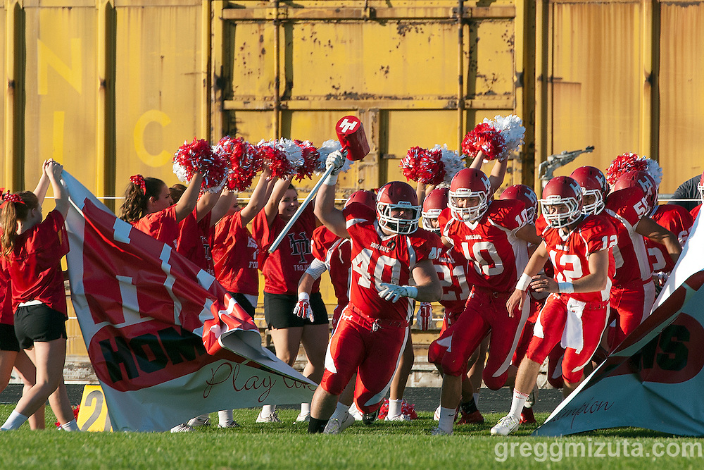 Homedale (L to R: Jakobee Osborn, Connor Carter, Lawsen Mattteson) charges onto the field before the start of the Vale - Homedale football game, September 11, 2015 at Homedale High School, Homedale, Idaho. Homedale won 40-7.