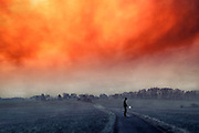 Man standing on a country road holding a lit torch under an orange morning sky...