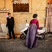 A couple in formal wedding attire returns home after a family member's wedding in Busan, South Korea.