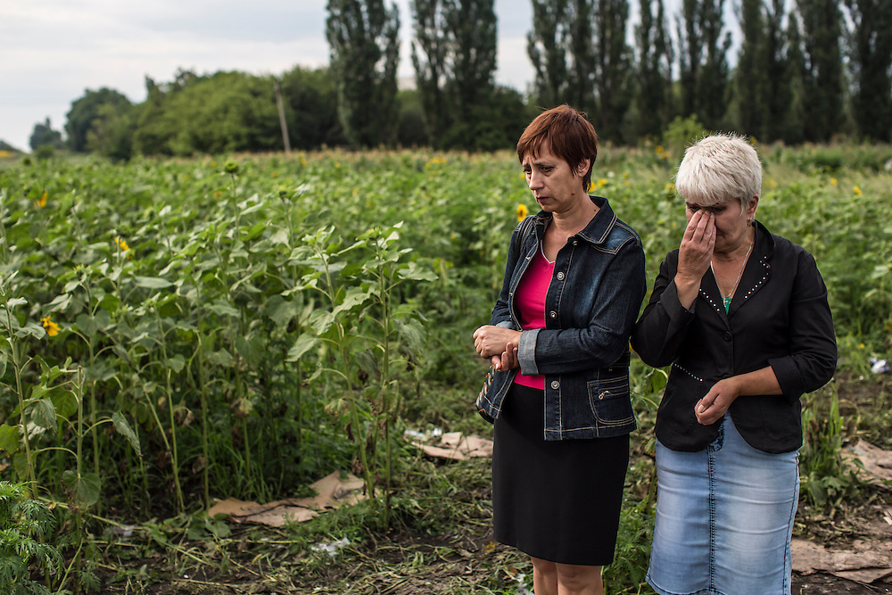 RASSIPNOYE, UKRAINE - JULY 19: Women visit the site where the cockpit of Malaysia Airlines flight MH 17 crashed in a field of sunflowers on July 19, 2014 in Rassipnoye, Ukraine. Malaysia Airlines flight MH17 was travelling from Amsterdam to Kuala Lumpur when it crashed killing all 298 on board including 80 children. The aircraft was allegedly shot down by a missile and investigations continue over the perpetrators of the attack. (Photo by Brendan Hoffman/Getty Images) *** Local Caption ***