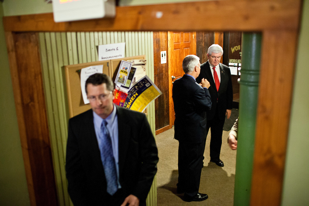 Republican presidential candidate Newt Gingrich, right, talks with staff at Smokey Row Coffee House on Tuesday, December 20, 2011 in Oskaloosa, IA.