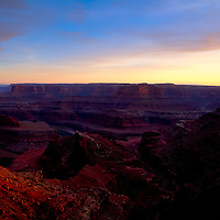 Warm light from the setting sun highlights Dead Horse Point over the Colorado River near Moab, Utah.