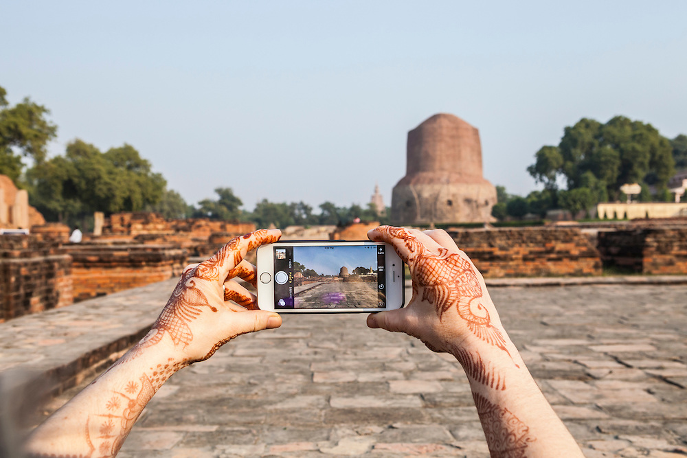 A woman taking a picture of Dhamekh Stupa in Sarnath, India with her iPhone.