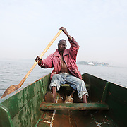 Augustino Ssekisaka rows out for the morning to set his fishing nets in Lake Victoria. Here in Ggaba, a small town in southern Uganda that almost entirely subsists on the fishing industry, the locals have contributed to the dangerous overfishing of the lake despite strict regulations from Tanzania, Uganda, and Kenya. Fishermen continue to keep fish that are far below the required minimum weight and employ dymanite and poison.