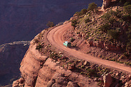 Distant view of a van driving uphill near the edge of a cliff on a steep part of the Shafer Trail in Canyonlands National Park, Utah.<br /> <br /> WATERMARKS WILL NOT APPEAR ON PRINTS OR LICENSED IMAGES.<br /> <br /> Licensing: https://tandemstock.com/assets/59162971