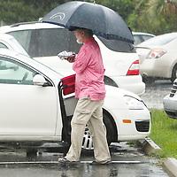 A man walks across a parking lot during a rain storm Thursday August 7, 2014 in Wrightsville Beach, N.C.  (Jason A. Frizzelle)