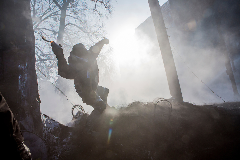 KIEV, UKRAINE - JANUARY 25: An anti-government protester throws a Molotov cocktail during clashes with police on Hrushevskoho Street near Dynamo stadium on January 25, 2014 in Kiev, Ukraine. After two months of primarily peaceful anti-government protests in the city center, new laws meant to end the protest movement have sparked violent clashes in recent days. (Photo by Brendan Hoffman/Getty Images) *** Local Caption ***