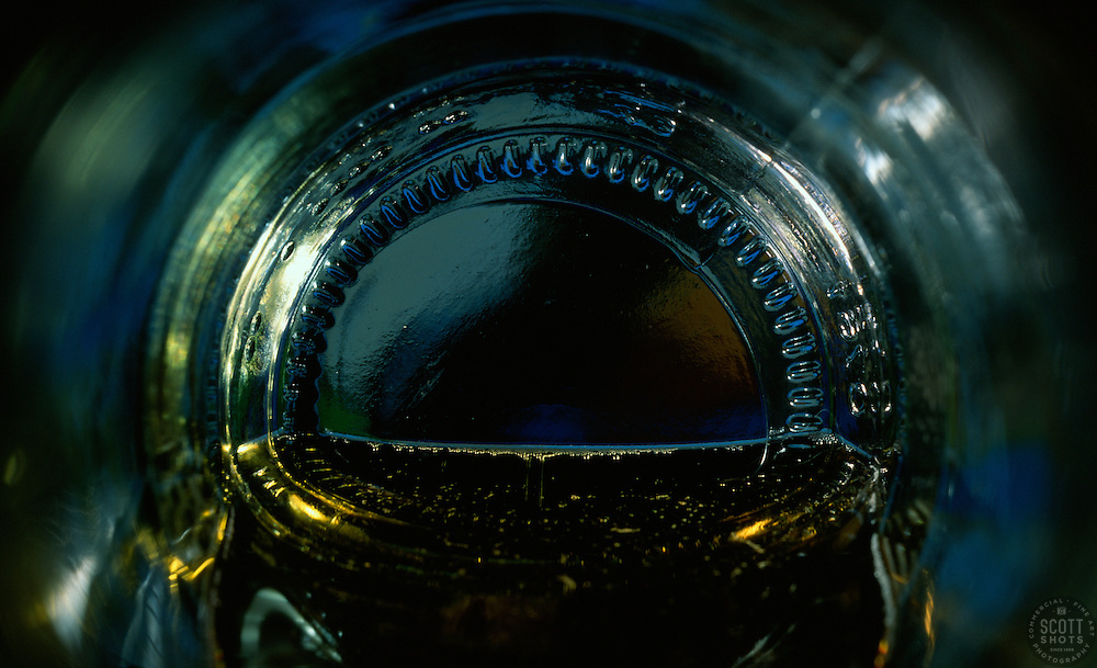 """Beauty at the Bottom: Dark Nights""- This image is a photograph of a beer bottle shot right down the mouth of the bottle. A television provides the main light source."