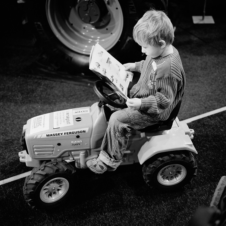 Tractor culture at Jaeren, Rogaland, Norway...A boy on a toy tractor studying a catalogue of toy machines at an agriculture show in Stavanger, Norway..Jaeren is one of the major agricultural areas in Norway. There are tractors and traces of tractors almost everywhere. ..Photo by Knut Egil Wang /MOMENT