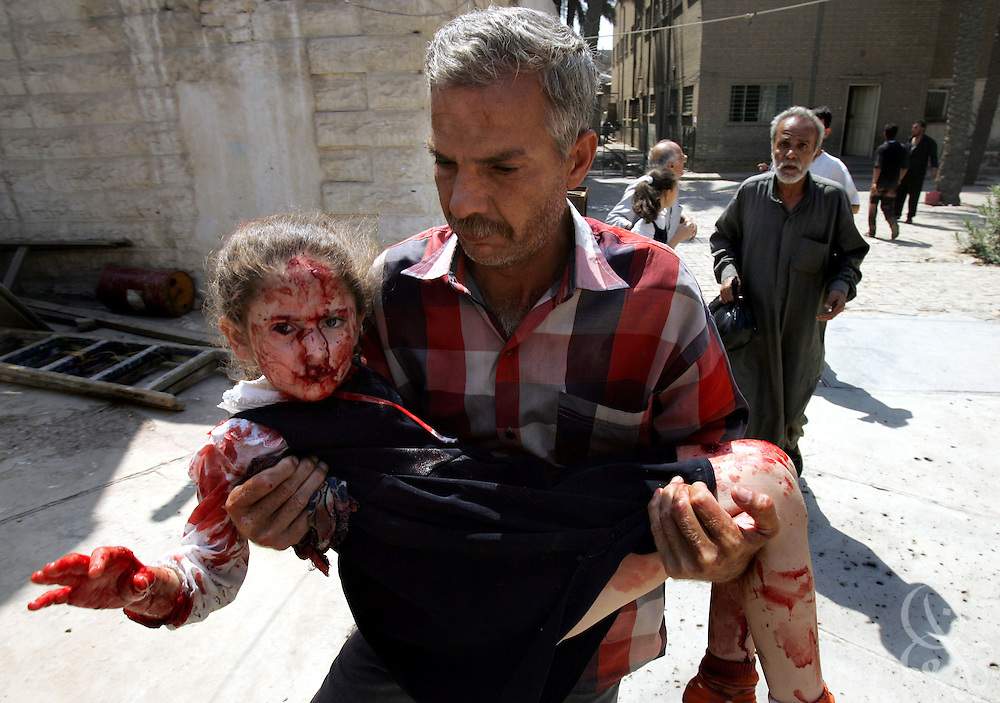 An injured Iraqi schoolgirl is evacuated from the Aqida girls' school near the scene of a suicide car bombing in Tahrir square in Baghdad May 7, 2005. The bombing, which targeted a passing civilian contractor convoy just outside the school killed at least 6 persons, and wounded another 30 in the late morning explosion in the busy commercial area in the center of Baghdad.