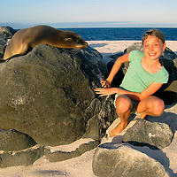 South America, Ecuador, Galapagos Islands. A young girl and a young seal lion pup in the Galapagos Islands.
