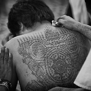 """A devotee, his back covered in Sak Yant tattoos is seen as he and others attend the annual """"Wai Kru"""" tattoo festival at Wat Bang Pra in Nakhon Chasi, Thailand Saturday, March 23, 2013.  Devotees attend the one day event to have their """"Sak Yant"""" religious tattoos energized by Buddhist monks and tattoo masters."""