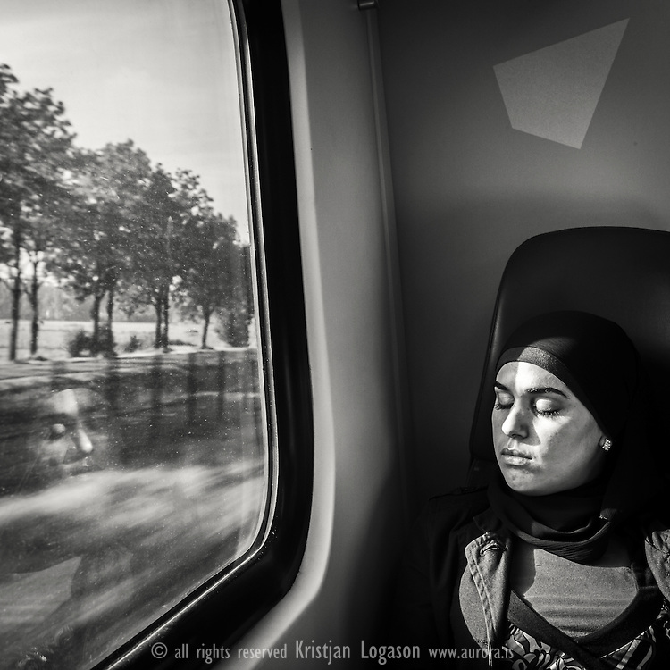 Woman feeling the warmth of the sun on her face during a trainride from Netherland to Germany