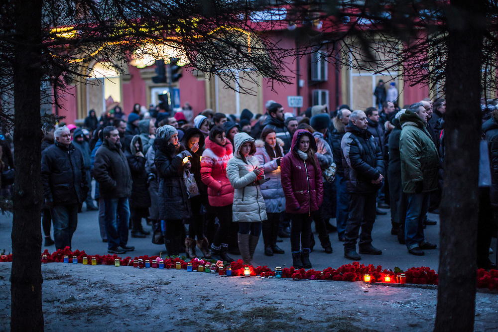 DONETSK, UKRAINE - JANUARY 24, 2015: People hold candles at a memorial event for victims of a rocket strike that hit a trolleybus two days earlier in Donetsk, Ukraine. The attack killed at least eight civilians and injured many more. CREDIT: Brendan Hoffman for The New York Times