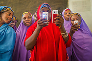Members of the Mada Saving Club in Tsafe Nigeria, checking cell phones.  The Club is for women and has over 5500 members. Every week, women give money and when they need it, they can borrow with  a small interest not payable until after the first month.