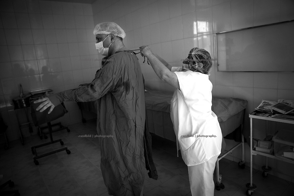 """During surgery in a new built operational room in the local hospital in Shushi. This image is part of the photoproject """"The Twentieth Spring"""", a portrait of caucasian town Shushi 20 years after its so called """"Liberation"""" by armenian fighters. In its more than two centuries old history Shushi was ruled by different powers like armeniens, persians, russian or aseris. In 1991 a fierce battle for Karabakhs independence from Azerbaijan began. During the breakdown of Sowjet Union armenians didn´t want to stay within the Republic of Azerbaijan anymore. 1992 armenians manage to takeover """"ancient armenian Shushi"""" and pushed out remained aseris forces which had operate a rocket base there. Since then Shushi became an """"armenian town"""" again. Today, 20 yeras after statement of Karabakhs independence Shushi tries to find it´s opportunities for it´s future. The less populated town is still affected by devastation and ruins by it´s violent history. Life is mostly a daily struggle for the inhabitants to get expenses covered, caused by a lack of jobs and almost no perspective for a sustainable economic development. Shushi depends on donations by diaspora armenians. On the other hand those donations have made it possible to rebuild a cultural centre, recover new asphalt roads and other infrastructure. 20 years after Shushis fall into armenian hands Babies get born and people won´t never be under aseris rule again. The bloody early 1990´s civil war has moved into the trenches of the frontline 20 kilometer away from Shushi where it stuck since 1994. The karabakh conflict is still not solved and could turn to an open war every day. Nonetheless life goes on on the south caucasian rocky tip above mountainious region of Karabakh where Shushi enthrones ever since centuries."""