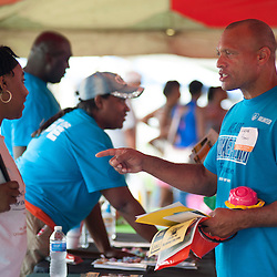 25 JULY 2015 -- FERGUSON, Mo. -- Pastor Aeneas Williams of The Spirit Church, a former St. Louis Ram and a member of the Pro Football Hall of Fame, visits with staff and volunteers staffing tables representing non-profit and public service agencies during Convoy of Hope, a faith-based outreach program at Forestwood Park in Ferguson, Mo. Saturday, July 25, 2015. The event included health check ups, haircuts, career counseling, play areas for children, food for needy families and spiritual counseling. Williams' church is in Valley Park, Mo.<br /> <br /> Photo by Sid Hastings.