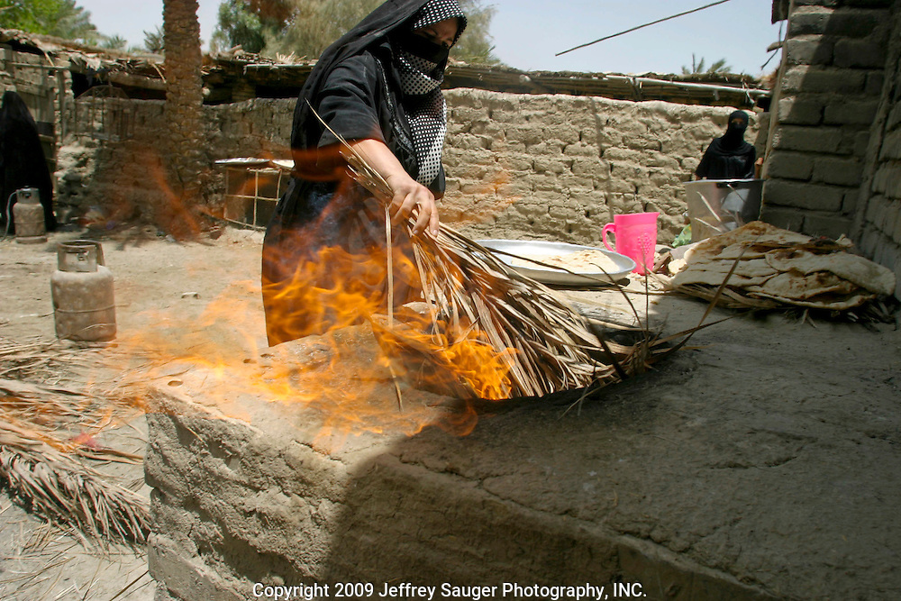 A woman fans the flames in an oven to make traditional Iraqi flat bread during the Al-Kasid family's Istikbal, or homecoming, in their home village Suq ash Shuyukh, about 20 miles southeast of Nasiriyah, Iraq, July 31, 2003...The women spend most of their time making dough, baking bread, milking cows, taking care of children, preparing food, etc. as the men gather out front of the compound. The women wear black as a sign of mourning for a close loved one that has died; some for a year and some forever after the death.