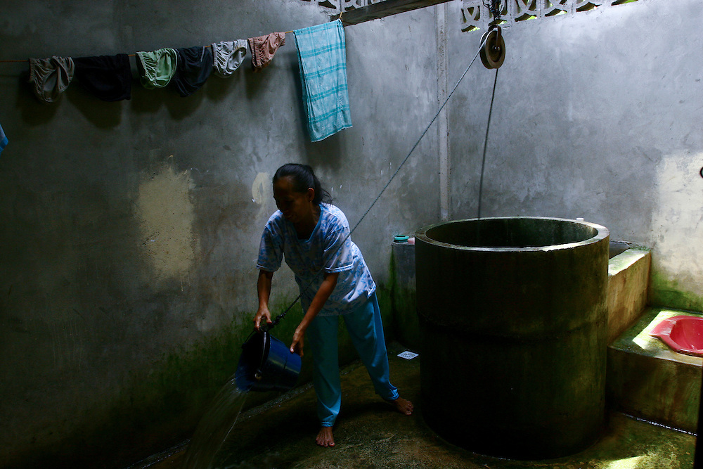 Woman by the well of her home in Banda Aceh. @ Martine Perret. February 2006