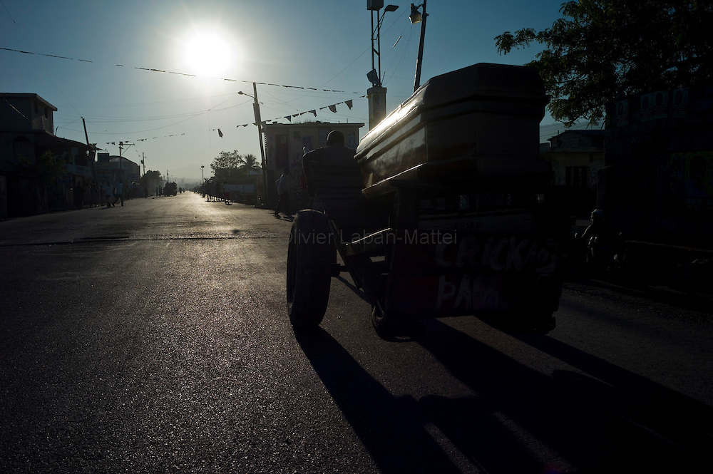 According to latest figures provided by the Haitian Ministry of Health, 1,100 people have already died from the epidemic of cholera./// A man carries a coffin in a street of Cite Soleil, the biggest slum of Port-au-Prince, hit by cholera.
