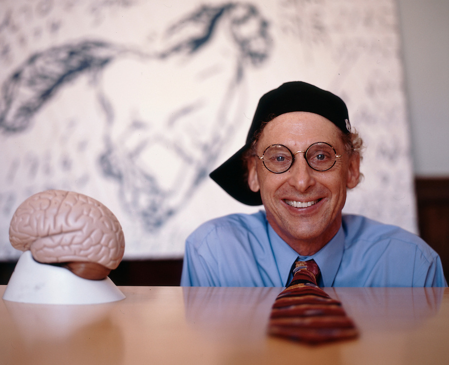 """Professor Alan Snyder of The Centre for the Mind at Sydney University with his """"think cap"""". The pictures on the wall were drawn by four year old autistic children...........Sydney, March 2003"""