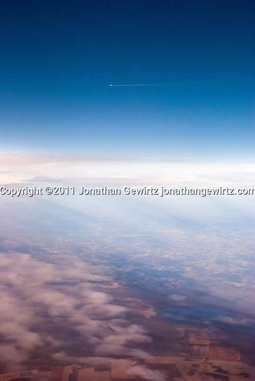 A distant jet aircraft with a contrail flies over a winter landscape. WATERMARKS WILL NOT APPEAR ON PRINTS OR LICENSED IMAGES.