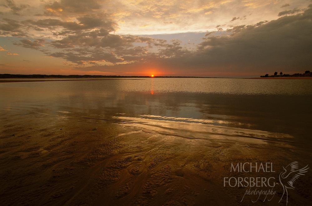 The sun sets behind the Calamus Reservoir, Nebraska Sandhills.