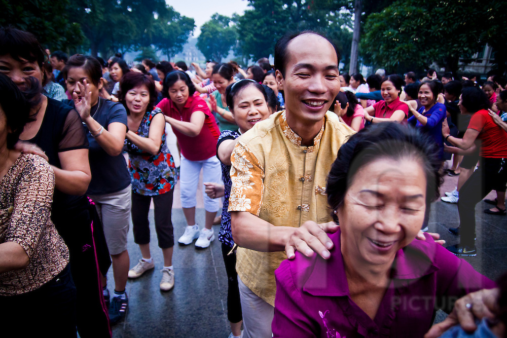 People practice 'laughing yoga' in the early morning in front of the statue of Ly Thai To in Hanoi, Vietnam, Asia