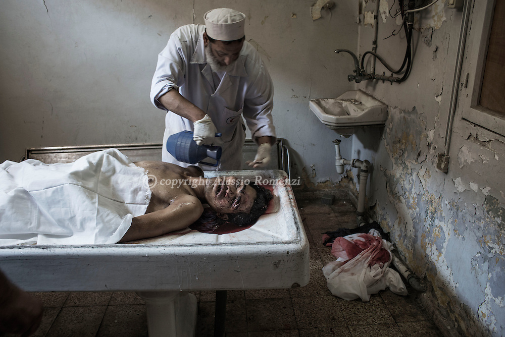 Gaza Strip, Khan Younis: Palestinians prepare the body of a Palestinian killed by an Israeli air strike on the outskirs of Khan Younis over night at the morgue at the hospital in Khan Younis Thursday, July 10, 2014. ALESSIO ROMENZI