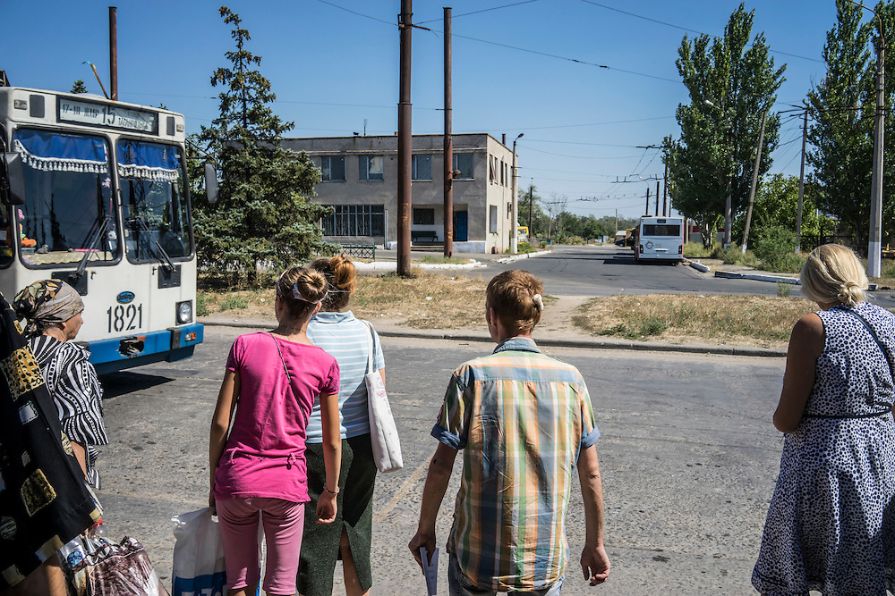 MARIUPOL, UKRAINE - AUGUST 31, 2015: People prepare to board a trolley bus in Mariupol, Ukraine. This eastern district of Mariupol, closer than downtown to the front lines, was hit by heavy shelling in January that killed approximately 30 people. CREDIT: Brendan Hoffman for The New York Times