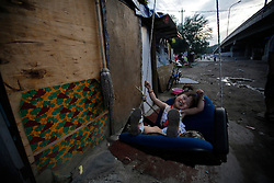 A picture made available on 30 July 2013 of 11month-old Chinese girl Shuangshuang having fun on a makeshift swing outside her home in a slum or shanty town area by the second ring road of Beijing, metres away from the prosperous Central Business District (CBD), separated only by a busy highway in China, 29 July 2013. Beijing announced plans to spend 500 billion yuan (61.5 billion euros) to renovate shanty towns within the fourth ring road according to local media. The five-year plan is expected to affect more than 230,000 households. China's massive urbanization push has resulted in the creation of large pockets of shanty towns and slums in urban areas as millions of migrant workers shifting to the cities are often priced out of city-centre properties. Slum or shanty town dwellers often live in dirty and cramped conditions, where they have no running water in their homes and have to share toilet and shower facilities.