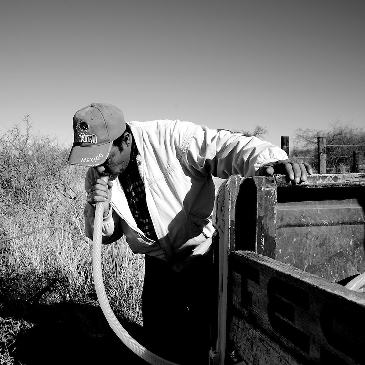 Fernando Lerma, a volunteer with the Migrant Resource Center, siphons water through a hose while filling water tanks in the desert near Naco, Sonora, Mexico, on Wednesday, Jan. 30, 2008. MRC is a bi-national project of Citizens for Border Solutions (Bisbee, AZ) and Iglesia del Camino (Naco, Mexico), with support of other organizations and individuals. In back is Esteban Perez.