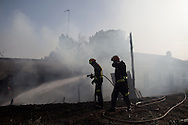 Madrid Community firefighters work on a forest fire that reached a house in San Agustin de Guadalix on August 11, 2012, near Madrid, Spain. During a heat wave dozens of forest fires have appeared in Spain, three of them at National Parks, like Teide, Doñana or Cabañeros, and also thousands of people had to be evacuated at La Gomera and Tenerife, in the Canary Islands.