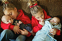 Acaja-Lyn Scott, left, and her twin sister Jillian-Kate relax with their baby brothers Brailey, left, and Sakiyas in their living room Tuesday in Coeur d'Alene.