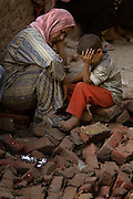 An Egyptian woman and her son sit amid the ruins of their home on the edge of a giant rock slide Saturday, September 06, 2008 in the Cairo shantytown of Manshiyet Nasr. At least 62 people were killed in the morning rockslide, but hundreds more are still buried and that number is sure to rise.