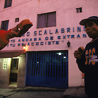 A migrant offers his breakfast to another outside the Casa Del Migrante shelter in Tijuana, Mexico, a temporary home for stranded and destitute migrants attempting to cross the border or for those recently deported. Migrants are forced out of the shelter at dawn to look for work.