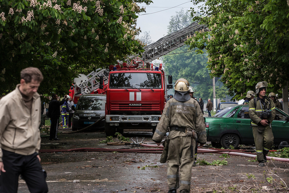MARIUPOL, UKRAINE - MAY 9: People watch as firemen work to put out a blaze at a police station which was attacked and burned on May 9, 2014 in Mariupol, Ukraine. Witnesses said that Ukrainian National Guard soldiers opened fire on police officers who refused orders to disperse a pro-Russia rally. (Photo by Brendan Hoffman/Getty Images) *** Local Caption ***