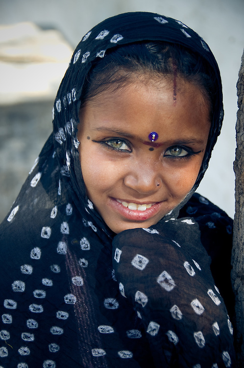 Portrait of a beautiful green-eyed Rajasthani girl wearing a head-scarf and traditional make-up (India)